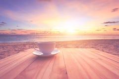 Copo de café na tabela de madeira no por do sol ou na praia do nascer do sol com lente fl Foto de Stock