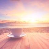 Copo de café na tabela de madeira no por do sol ou na praia do nascer do sol com lente fl Fotos de Stock