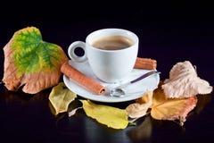 Copo de café na tabela de madeira preta com folhas de outono Fotografia de Stock