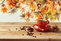 Copo de café na tabela de madeira sobre o fundo das folhas de outono Imagem de Stock