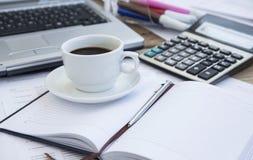 Copo de café no escritório com papéis financeiros, agenda e calculadora imagens de stock royalty free