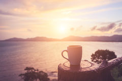 Copo de café no por do sol ou na praia do nascer do sol no com alargamento da lente WA Fotos de Stock Royalty Free