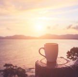 Copo de café no por do sol ou na praia do nascer do sol no com alargamento da lente WA Imagem de Stock