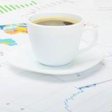 Copo de café sobre a carta financeira - tiro ascendente próximo do estúdio Imagem de Stock Royalty Free