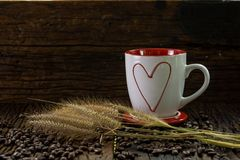 Copo de café vermelho e branco com teste padrão da forma do coração, flores da grama seca e feijões de café na tabela de madeira Imagem de Stock