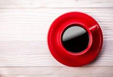 Copo de café vermelho na tabela de madeira clara Imagem de Stock Royalty Free