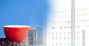 Copo de café vermelho no pano de tabela vermelho e branco com os feijões contra o fundo azul e o tra obscuro do escritório Fotografia de Stock Royalty Free