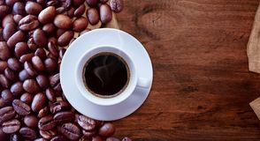Copo de caf? e feij?es de caf? no estilo de madeira do vintage do fundo da tabela para o projeto gr?fico fotos de stock