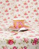 Copo de chá antigo completamente do chá no fundo floral Fotos de Stock