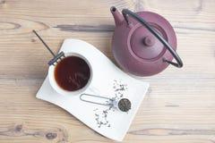 Copo de chá branco da porcelana, bule do ferro fundido e chá preto a parte superior vie fotografia de stock