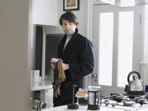 Copo de chá de secagem do homem com a toalha na cozinha Foto de Stock