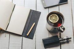 Copo de chá, telefone celular, caderno, lápis e cigarro eletrônico para vaping fotos de stock