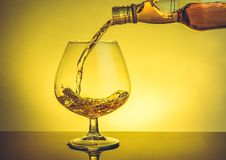Copo de conhaque de derramamento do empregado de bar da aguardente no vidro típico elegante do conhaque na tabela Fotografia de Stock