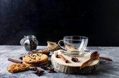 Copo de Emply para o chá, biscoitos, canela, anis no backgrou escuro Foto de Stock