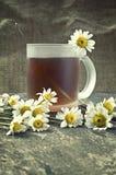 Copo de flores do chá e da camomila Fotografia de Stock Royalty Free