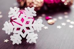 Copo de nieve blanco en el fondo de las chucherías de Navidad de la magenta y del oro Foto de archivo