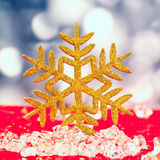 Copo de nieve de oro de la Navidad en los cubos de hielo Imagen de archivo
