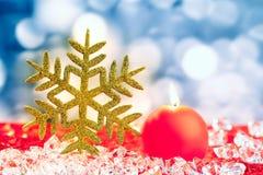 Copo de nieve de oro de la Navidad en los cubos de hielo Foto de archivo