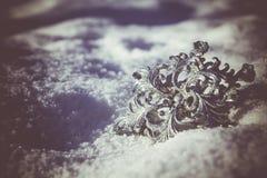 Copo de nieve de plata en la nieve retra foto de archivo
