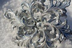 Copo de nieve de plata en nieve imágenes de archivo libres de regalías