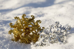 Copo de nieve del oro y de la plata en nieve imagen de archivo libre de regalías