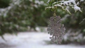 Copo de nieve de la decoración de la Navidad que cuelga en el árbol de abeto nevoso, a cámara lenta almacen de video