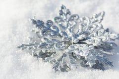 Copo de nieve plateado del juguete del ` s del Año Nuevo en la nieve, Imagenes de archivo