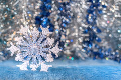 Copo de nieve translúcido del juguete de la Navidad en backgro plata-azul del bokeh Imagen de archivo libre de regalías