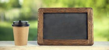 Copo de papel do café com placa de giz, na tabela de madeira, fundo do dia de verão imagens de stock royalty free