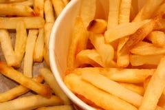 Copo de papel enchido com as batatas fritas A metade do copo é considerada na foto Cercado por batatas fritas friáveis em uma fol imagem de stock royalty free