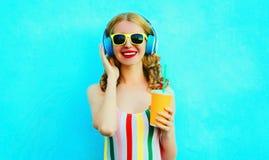 Copo de sorriso feliz da terra arrendada da mulher do retrato do suco que escuta a música em fones de ouvido sem fio no azul colo imagens de stock