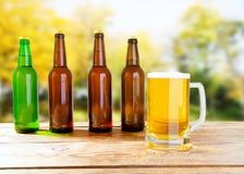 Copo de vidro grande da cerveja na tabela de madeira velha no fundo borrado do parque imagens de stock royalty free