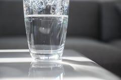 Copo de vidro meio cheio na tabela de mármore Fotografia de Stock Royalty Free