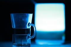 Copo de vidro na luz azul encantador foto de stock royalty free