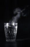 Copo de vidro transparente com inchamento a água a ferver nela O vapor da parte superior Fundo preto fotos de stock royalty free