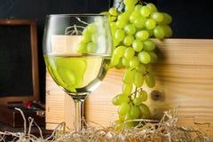 Copo de vinho branco e grupos brancos do verde amarelo de uvas da baga com a garrafa do vinho foto de stock