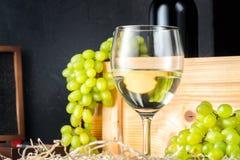 Copo de vinho branco e grupos brancos do verde amarelo de uvas da baga com a garrafa do vinho fotos de stock royalty free