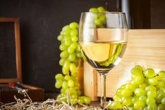 Copo de vinho branco e grupos brancos do verde amarelo de uvas da baga com a garrafa do vinho imagem de stock