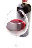 Copo de vinho com vinho tinto e garrafa no fundo branco Fotos de Stock Royalty Free