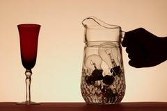 Copo de vinho e mão que tomam o jarro de ampolas fotos de stock royalty free