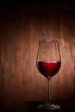 Copo de vinho frágil meio cheio do vinho tinto que está em um fundo de madeira Imagens de Stock
