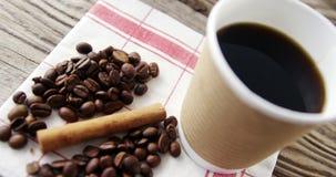 Copo descartável com feijões e canela de café na prancha de madeira filme