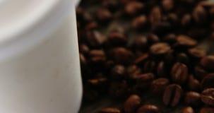 Copo descartável com os feijões de café na prancha de madeira filme