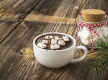 Copo do cacau caseiro perfumado com marshmallows e cobertura branca vermelha esmagada dos doces No estrutural de madeira simples foto de stock