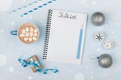 Copo do cacau, do presente, de decorações quentes do feriado e do caderno com para fazer a lista na tabela azul do vintage de cim Foto de Stock
