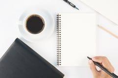 Copo do caderno quente da escrita da mão do café e do homem no backgr branco Imagens de Stock Royalty Free