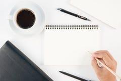 Copo do caderno quente da escrita da mão do café e do homem no backgr branco Imagens de Stock
