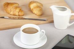 Copo do café branco com os croissant dourados frescos Imagens de Stock