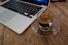 Copo do café com o portátil na tabela de madeira Fotos de Stock