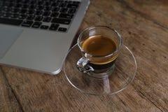Copo do café com o portátil na tabela de madeira Imagens de Stock